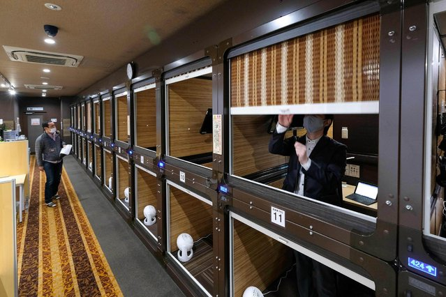 This picture taken on November 27, 2020 shows a floor of the capsule hotel Anshin Oyado Shinjuku, Tokyo, which has been renovated into a coworking space without the upper and lower partitions of the capsule. Facing unprecendented challenges due to the Covid-19 coronavirus pandemic, the capsule hotel renovated an entire floor to be used as a coworking space - offering office necessities such as high speed internet required for telework and web conferencing, including computer hardware and other computing devices. (Photo by Kazuhiro Nogi/AFP Photo)