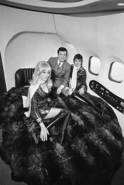 "In this February 17, 1970 file photo, Playboy empire magnate Hugh Hefner, center, poses with two of the Playboy Jet Bunnies on large six foot by eight foot elliptical bed after his new $5.5 million aircraft arrived at Burbank Airport in Burbank, Calif. The bed is in Hefner's private quarters in the rear section of the ""Big Bunny"" plane. (Photo by George Brich/AP Photo)"