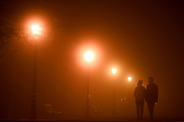 A couple walk in the Retiro park in Madrid on November 17, 2020 as a thick fog falls on the Spanish capital. (Photo by Gabriel Bouys/AFP Photo)