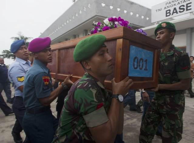Indonesian military carry a casket containing the body of a AirAsia flight QZ8501 passenger recovered off the coast of Borneo at a Military base in Surabaya December 31, 2014. Indonesian rescuers searching for an AirAsia plane carrying 162 people pulled bodies and wreckage from the sea off the coast of Borneo on Tuesday, prompting relatives of those on board watching TV footage to break down in tears. (Photo by Sigit Pamungkas/Reuters)