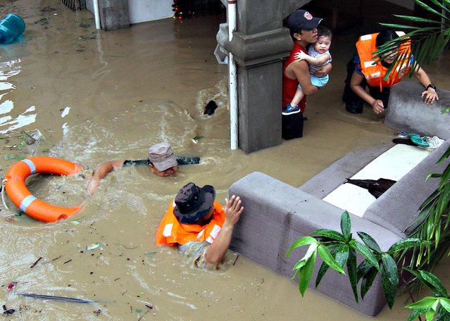 Policemen evacuate families trapped in their home during heavy flooding brought by tropical storm Seniang in Misamis Oriental, Mindanao island in southern Philippines December 29, 2014. Local media reported three people were killed, while more than 10,000 residents were evacuated due to heavy flooding in some parts of Mindanao in southern Philippines. (Photo by Erwin Frames/Reuters)