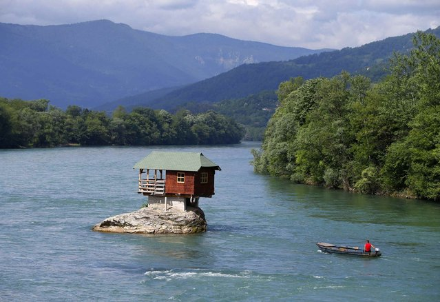 A man rows a boat near a house built on a rock on the river Drina near the western Serbian town of Bajina Basta, about 160km (99 miles) from the capital Belgrade May 22, 2013. (Photo by Marko Djurica/Reuters)