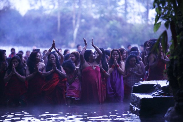 Devotees offer prayers as they submerge themselves in the river before taking a holy bath at Saali River during the first day of the Swasthani Brata Katha festival at Sankhu in Kathmandu January 5, 2015. (Photo by Navesh Chitrakar/Reuters)