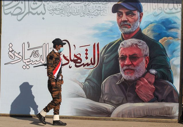An Iraqi fighter of the Hashed al Shaabi (Popular Mobilisation) paramilitary units walks past a poster depicting late Iraqi commander Abu Mahdi al-Muhandis (R) and Iranian Revolutionary Guards commander Qasem Soleimani, in the capital Baghdad on December 30, 2020, ahead of the first anniversary of their killing in a US drone attack. On January 3, Iraq will mark a year since a US drone strike killed al-Muhandis, the deputy head of Iraq's powerful Tehran-aligned Hashed Al-Shaabi paramilitary network, alongside Soleimani, head of the elite external operations of Iran's Revolutionary Guards, nearly sparking a conflict that many fear could still ignite. (Photo by Ahmad Al-Rubaye/AFP Photo)