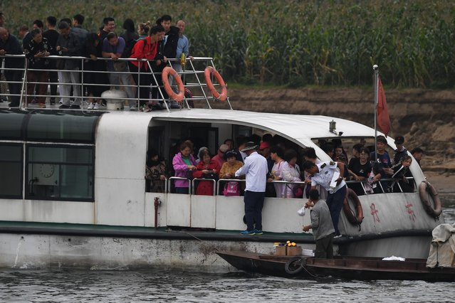 "A North Korean man (bottom R) sells items to Chinese tourists on the Yalu river near the North Korean town of Sinuiju, opposite the Chinese border city of Dandong, in China's northeast Liaoning province on September 5, 2017. The US has accused North Korea of ""begging for war"" and pushed for the ""strongest possible measures"" on Pyongyang following its sixth and most powerful nuclear test. (Photo by Greg Baker/AFP Photo)"