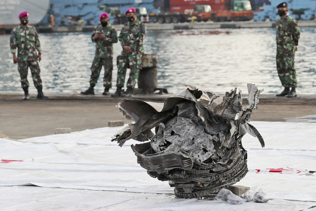 Indonesian marines look at a large part of a plane recovered from the waters off Java Island where Sriwijaya Air flight SJ-182 crashed on Saturday, at Tanjung Priok Port in Jakarta, Indonesia, Monday, January 11, 2021. The search for the black boxes of the crashed Sriwijaya Air jet intensified Monday to boost the investigation into what caused the plane carrying 62 people to nosedive at high velocity into the Java Sea. (Photo by Tatan Syuflana/AP Photo)
