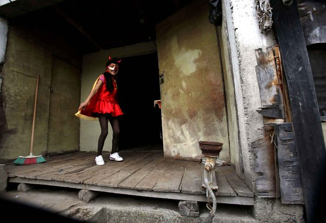 A girl practices her dance steps before participating in the traditional parade of La Diablada en Pillaro, Ecuador, Sunday, January 4, 2015. Originally people dressed in devil costumes where used to open up space to allow other participants to dance, but over the years the character gained popularity and became the most popular costume of the feast. (Photo by Dolores Ochoa/AP Photo)