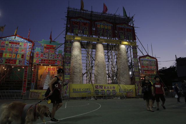 People walk in front of the bun towers on the outlying Cheung Chau island in Hong Kong, Tuesday, May 22, 2018 to celebrate the Bun Festival. (Photo by Kin Cheung/AP Photo)