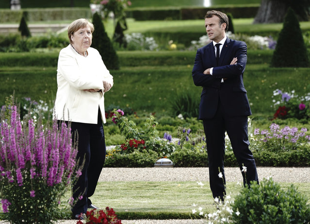 French President Emmanuel Macron talks to German Chancellor Angela Merkel during a meeting at Meseberg Castle, the German government's guest house in Meseberg, Germany, June 29, 2020. One of the topics of the meeting is the European reconstruction plan of 750 billion euros in the Corona crisis. (Photo by Kay Nietfeld/dpa via AP Photo)