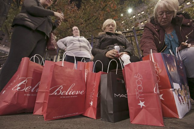 Women sit outside after shopping at Macy's Herald Square store during the early opening of the Black Friday sales in the Manhattan borough of New York, November 26, 2015. (Photo by Andrew Kelly/Reuters)
