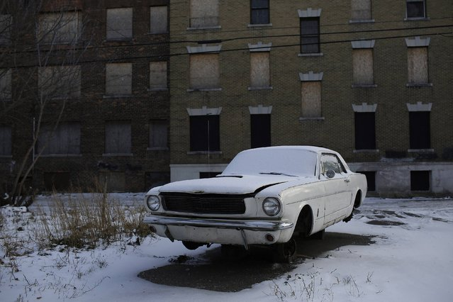 An older model Ford Mustang sits on cinder blocks with missing wheels near an abandoned apartment building in Detroit, Michigan January 7, 2015. Detroit, also known as the Motor City, is the historic hub of automobile manufacturing in the United States. (Photo by Joshua Lott/Reuters)