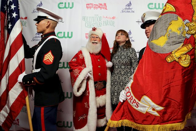 A Santa Claus character and Kennedy Slocum of the Nickelodeon show WITS Academy are flanked by members of the Marine Color Guard 3rd ANGLICO as they arrive to participate in the 84th Annual Hollywood Christmas Parade in the Hollywood section of Los Angeles, California, November 29, 2015. (Photo by David McNew/Reuters)