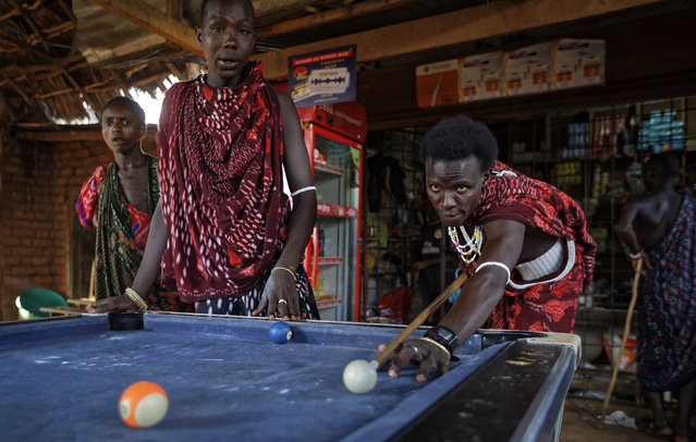 In this Friday, March 23, 2018 file photo, young Maasai men relax and play a game of pool at a bar by the side of the road in the late afternoon at Mkata junction, near Mikumi National Park in Tanzania. A U.S.-based group said Thursday, May 10, 2018 that tens of thousands of Tanzania's ethnic Maasai people have been left homeless after their houses were burned to keep the savannah open for tourism benefiting foreign safari companies. (Photo by Ben Curtis/AP Photo)