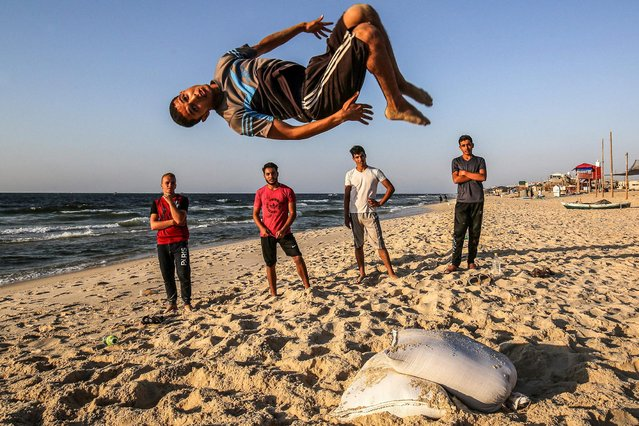 A youth performs a flip as others watch along a beach by the Mediterranean Sea shore in Rafah in the southern Gaza Strip at sunset on September 2, 2020. (Photo by Said Khatib/AFP Photo)