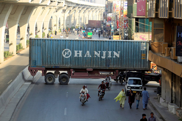 Motorcyclists pass through a gap in a barricade set up using shipping containers near the venue of a planned protest gathering organised by Awami Muslim League (AML), a political ally party of Imran Khan's Pakistan Tehreek-e-Insaf (PTI), in Rawalpindi, Pakistan, October 28, 2016. (Photo by Faisal Mahmood/Reuters)