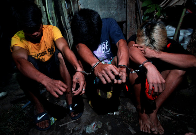 Men are handcuffed after they were detained by police during a police anti-illegal drugs operation in Quezon city, Metro Manila, Philippines November 9, 2016. (Photo by Czar Dancel/Reuters)