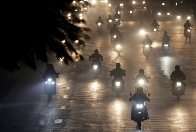 People commute on motorbikes during a smoggy evening as the air quality of Kathmandu reaches hazardous levels, Nepal on January 4, 2021. (Photo by Navesh Chitrakar/Reuters)