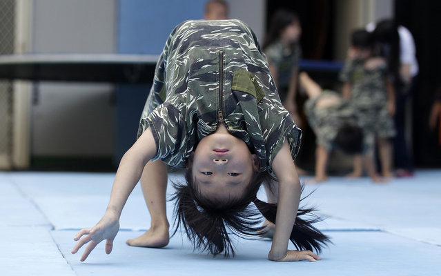 Kids in camouflage clothes attend a physical training session in a kindergarten in Taichung, central Taiwan, July 15, 2013. A kindergarten in Taiwan provides physical training sessions, a series of exercises that combines marine drills and gymnastics for pre-school and school aged kids. The training helps children grow well in both mind and body, according to the principal. (Photo by Pichi Chuang/Reuters)