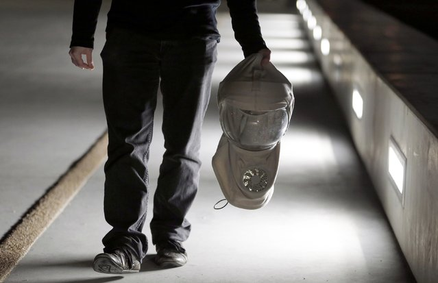 French twin Thomas Seris holds his protective head gear as he walks in the street in Bordeaux, December 12, 2014. (Photo by Regis Duvignau/Reuters)