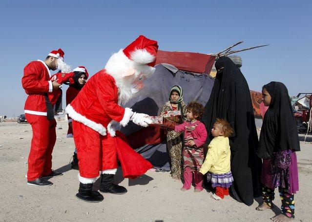 Volunteers wearing Santa Claus costumes distribute presents to children at a poor neighborhood in Najaf, south of Baghdad, December 19, 2015. (Photo by Alaa Al-Marjani/Reuters)