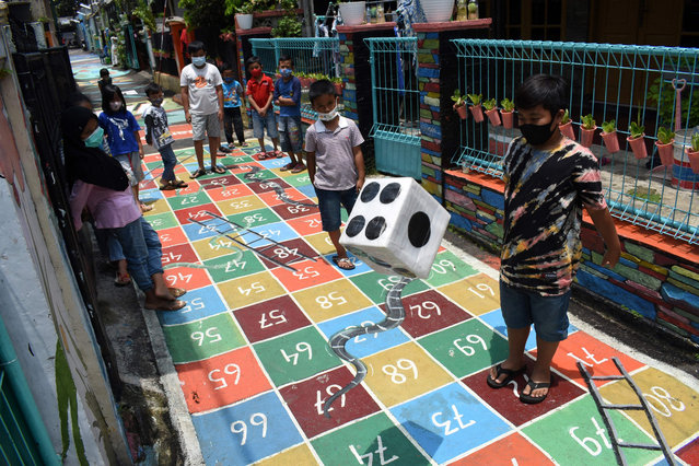 Children gather to play along a path painted with various children's games at a neighbourhood in Bandung on March 4, 2021. (Photo by Timur Matahari/AFP Photo)