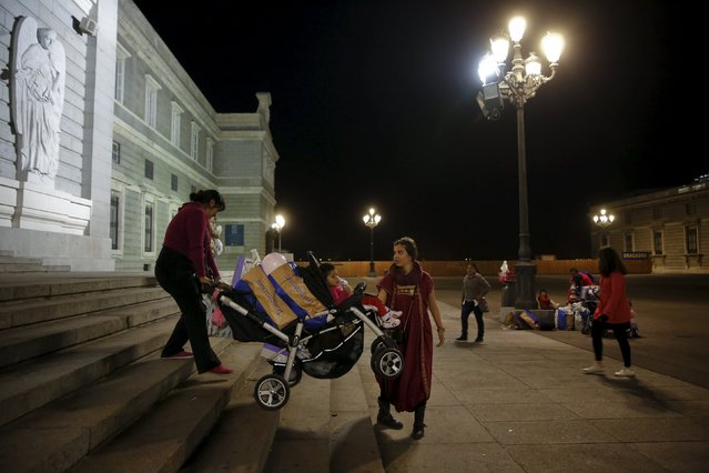 A volunteer dressed as one of the pages of the Three Wise Men helps a woman carry her stroller full of presents after a distribution of free toys for low-income families at Almudena Cathedral in Madrid, Spain, December 22, 2015. (Photo by Susana Vera/Reuters)