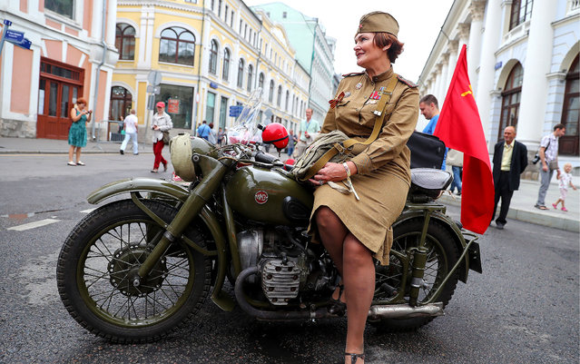 A woman dressed as WWII Red Army soldier sits on a Ural M-62 motorcycle in Ilyinka Street before the start of the 2018 GUM Gorkyclassic Motor Rally featuring classic cars in Moscow, Russia on July 21, 2018. (Photo by Anton Novoderezhkin/TASS via Getty Images)