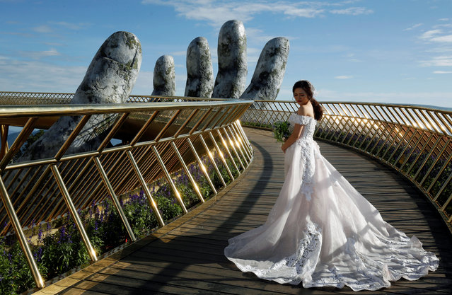 A Vietnamese bride poses for her wedding photos on Gold Bridge on Ba Na hill near Danang city, Vietnam on August 1, 2018. (Photo by Reuters/Kham)