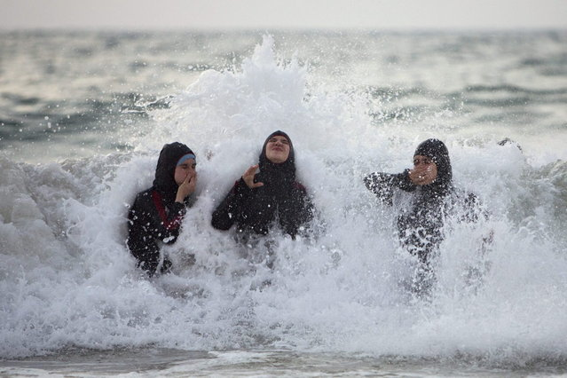 Palestinian women enjoy the Mediterranean sea during the Eid al-Fitr holiday, in Tel Aviv, Israel, Saturday, August 10, 2013. The three-day Eid al-Fitr holiday marks the end of the holy fasting month of Ramadan. One of the most important holidays in the Muslim world, Eid al-Fitr, is marked with prayers, family reunions and other festivities. (Photo by Oded Balilty/AP Photo)
