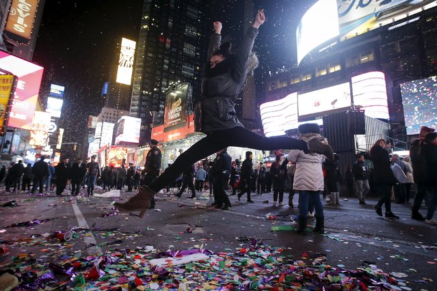 A woman jumps in the air as she poses for a photo during New Year celebrations in the Manhattan borough of New York, January 1, 2016. (Photo by Carlo Allegri/Reuters)