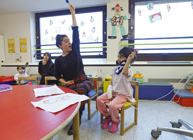 Zeinab (R) from Lebanon imitates musician Orphise as they both raise maracas at the pediatric department of the Hopital Erasme at the Universite Libre de Bruxelles (ULB), in Brussels, January 22, 2015. (Photo by Yves Herman/Reuters)