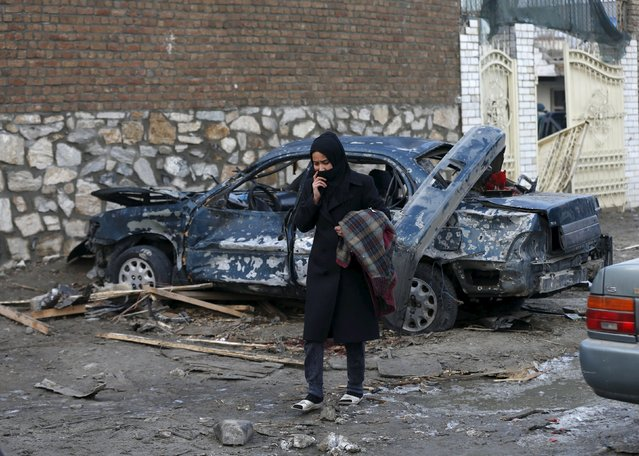 """An Afghan woman walks past a damaged car after a suicide attack on French restaurant  """"Le Jardin""""  in Kabul, Afghanistan January 2, 2016. (Photo by Mohammad Ismail/Reuters)"""