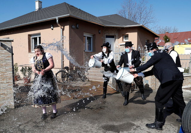 Members of the Hungarian dance and folk art ensemble Marcal throw water at a woman as part of traditional Easter celebrations in Gyor-Menfocsanak, Hungary, April 5, 2021. (Photo by Bernadett Szabo/Reuters)