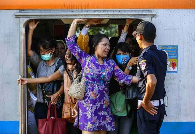 Women push themselves into a train car at Sudimara train station on the outskirts of Jakarta, Indonesia, on August 23, 2013. (Photo by Beawiharta/Reuters)