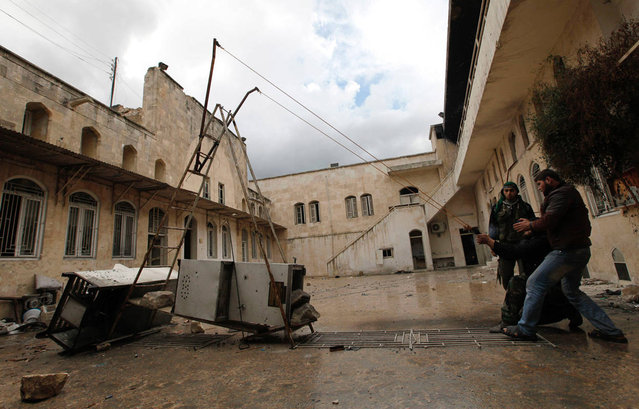 """""""Free Syrian Army"""" fighters use a homemade slingshot in old Aleppo, on January 29, 2013. (Photo by Zain Karam/Reuters)"""
