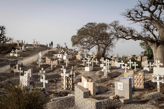 People walk through a mixed Catholic and Muslim cemetery in Fadiouth, Senegal on April 3, 2021. (Photo by John Wessels/AFP Photo)