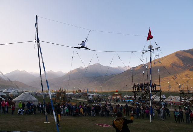 A boy runs a fast-paced high-wire act. The young man ascended the single rope on the left backward without a safety cord, though he harnessed himself in for his trick runs. (Photo by Amos Chapple/Radio Free Europe/Radio Liberty)