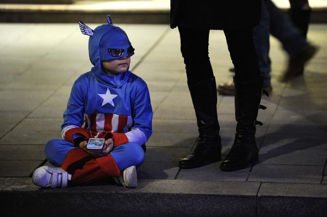 A boy dressed as Captain America plays with a mobile phone before the start of the Carnival parade in Gijon, northern Spain,  February 17, 2015. (Photo by Eloy Alonso/Reuters)