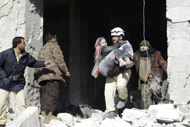 A civil defence member carries an injured woman in a site hit by what activists said were airstrikes carried out by the Russian air force in the rebel-controlled area of Maaret al-Numan town in Idlib province, Syria January 9, 2016. At least 70 people died in what activists said where four vacuum bombs dropped by the Russian air force in the town of Maaret al-Numan; other air strikes where also carried out in the towns of Saraqib, Khan Sheikhoun and Maar Dabseh, in Idlib. (Photo by Khalil Ashawi/Reuters)