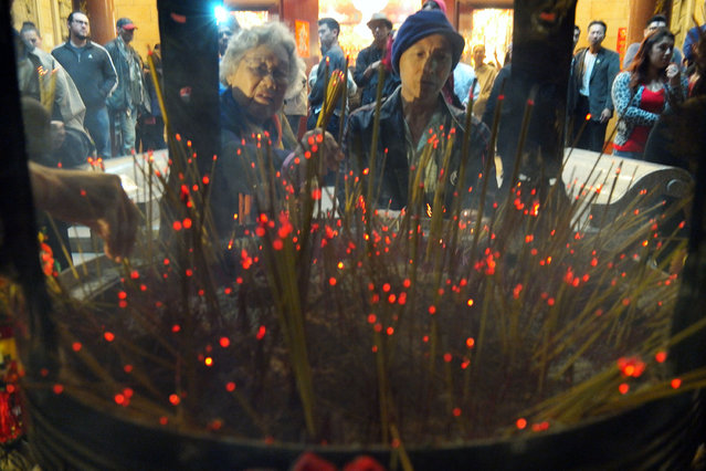 Temple goers burn incense Thursday, February 19, 2015 as they pray for health and fortune on the first day of the Chinese  and Vietnamese  Lunar New Year, the Year of the Sheep, at Thien Hau Pagoda in Los Angeles. (Photo by Nick Ut/AP Photo)