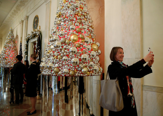 A woman takes a photo in the Cross Hall during a holiday decor preview of the White House in Washington, U.S., November 29,  2016. (Photo by Kevin Lamarque/Reuters)