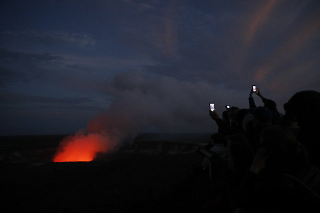 In this May 9, 2018, file photo, visitors take pictures as Kilauea's summit crater glows red in Volcanoes National Park, Hawaii. The small, rural town of Pahoa is the gateway to the eruption pouring rivers of lava out of Hawaii's Kilauea volcano. However, tourists are avoiding it because the county, citing safety concerns, isn't allowing the public to get close enough to the lava. (Photo by Jae C. Hong/AP Photo)
