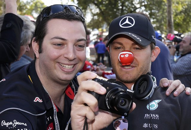 Mercedes Formula One driver Nico Rosberg of Germany wears a red nose for 'Red Nose Day' as he takes a photograph with a fan upon arrival for the first practice session of the Australian F1 Grand Prix at the Albert Park circuit in Melbourne March 13, 2015.  REUTERS/Mark Dadswell