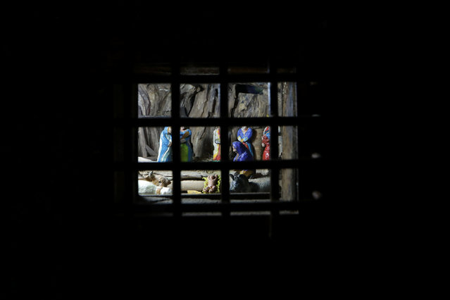 A Nativity scene is seen through an iron window door in the medieval mountain village of Luceram as part of Christmas holiday season, France, December 15, 2016. (Photo by Eric Gaillard/Reuters)