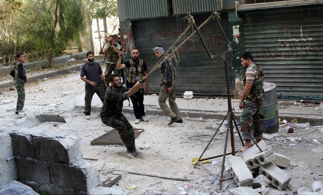 Members of the free Syrian Army use a catapult to launch a homemade bomb during clashes with pro-government soldiers in the city of Aleppo, October, 15, 2012. (Photo by Asmaa Waguih/Reuters)