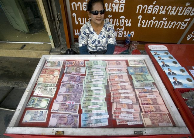 A woman displays Thai baht currency notes and memorial coins for sale to collectors outside the building which houses Thailand's central bank in Bangkok in this April 21, 2010 file photo. Thailand is expected to review interest rates this week. (Photo by Vivek Prakash/Reuters)