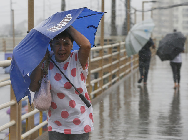 People brave the rain and wind brought about by typhoon Nock-Ten a day after Christmas Monday, December 26, 2016. (Photo by Aaron Favila/AP Photo)