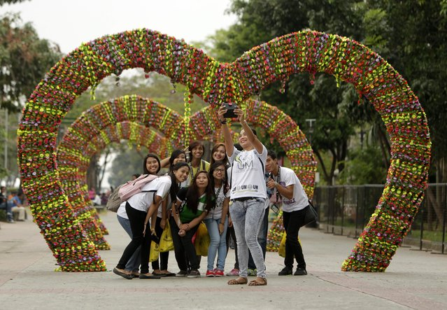 Filipinos take a selfie photo in front of a flower heart installation on the eve of Valentine's Day in a Park in Manila, Philippines, 13 February 2015. (Photo by Ritchie B. Tongo/EPA)