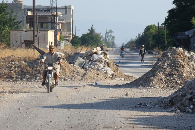 """Men ride their motorbikes past sand barricades after fighters from an alliance of insurgents known as the """"Army of Fatah"""" (Islamic Conquest)  took control of al-Ziyara village from forces loyal to Syria's President Bashar al-Assad, in Hama province, Syria August 10, 2015. (Photo by Ammar Abdullah/Reuters)"""