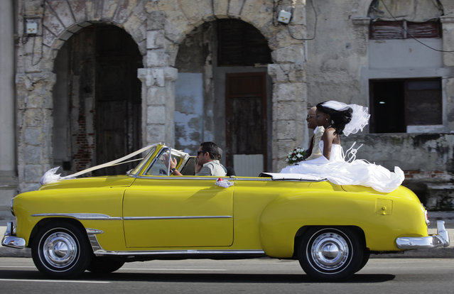 """A bride and groom ride a convertible car during wedding celebrations on Havana's seafront boulevard """"El Malecon"""" November 16, 2013. (Photo by esmond Boylan/Reuters)"""